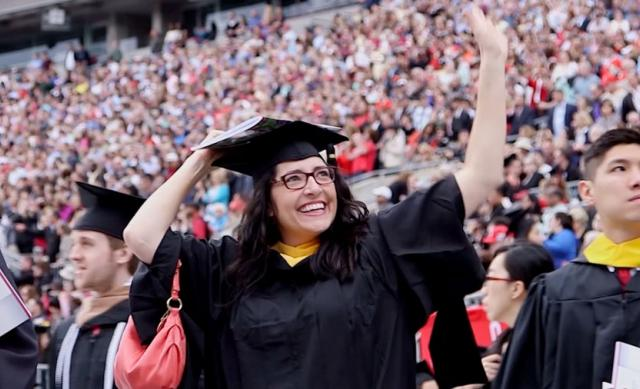 Student waves at graduation